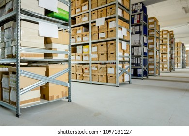 Stacks of files and paperwork placed in bookshelves with folders and documents in cardboard box archive, storage room.