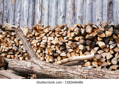 Stacks of firewood in the sawmill. Pile of firewood. Firewood background