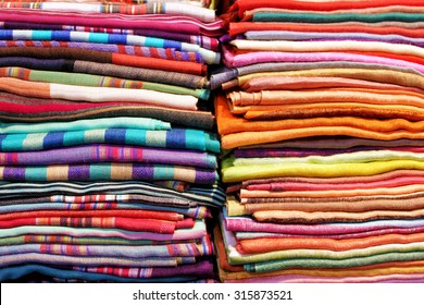 Stacks of folded colorful fabrics and textile close up background