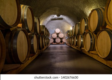 Stacks of French Oak Wine Barrel Casks made of Wooden Slaves and Bound by Metal Hoops in Old Wine Cellar.