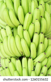 Stacks of fresh Green Cavendish banana in a fruit market produce
