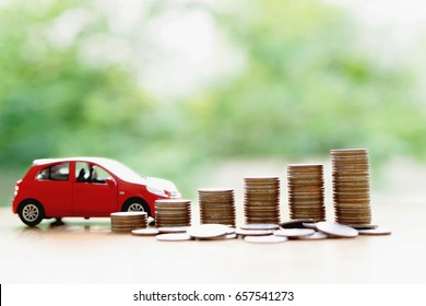 Stacks of giant silver coins next to a new red car
