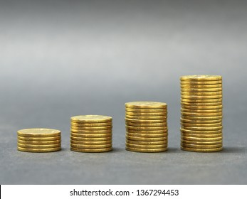 Stacks of golden coins in ascending order against dark background. Grooved edge of coins. Growth of economy, concept.