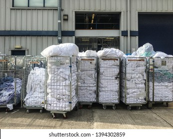 Stacks of laundry and linens waiting in trolleys before industrial cleaning outside of a warehouse