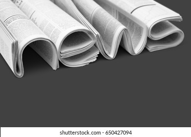 Stacks of modern newspapers, composed in form of word NEWS on gray background. Concept of news of world events