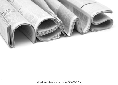 Stacks of modern newspapers, composed in form of word NEWS on white background. Concept of business news