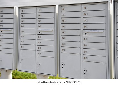 Stacks of multiple locked mail receptacles with slots for depositing mail, all located outside.