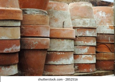 Stacks of old terra cotta flower pots in a gardening shed