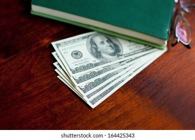 Stacks of one hundred dollars banknotes, notebook, pen and glasses on wooden desk
