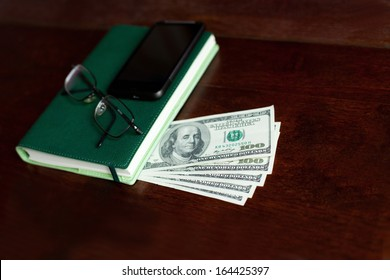 Stacks of one hundred dollars banknotes, notebook, pen and glasses on wooden desk