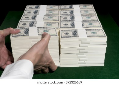 Stacks of one million US dollars in hundred dollar banknotes on green table.