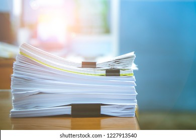 Stacks of paper files work desk office, business report papers,piles of unfinished documents achieves with clips indoor,Business concept.