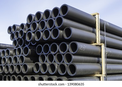 Stacks of plastic pipe in a construction yard with blue sky.