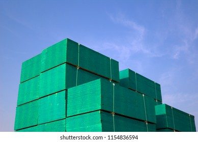 Stacks of plywood are highlighted against a blue sky in a manufacturer's plant.