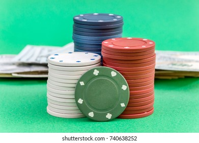 Stacks of poker chips with heap of money on the green background.