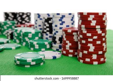 piles de puces de poker sur table verte et arrière-plan blanc