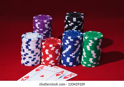 Stacks of Poker Chips with Playing Cards, closeup on red background