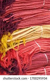 Stacks of red and yellow fabrics at the Ghanta Ghar, the Clock Tower market of Jodhpur, Rajasthan, India