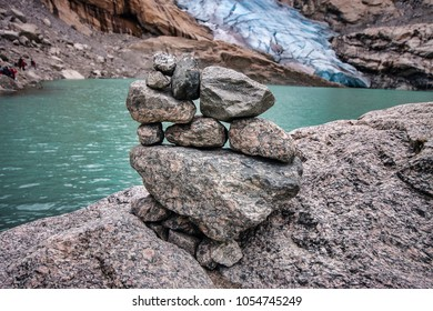 Stacks of rock cairns at Briksdalsbreen Glacier. You can see part of the glacier in the background