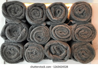 Stacks of rolled up grey towels in a spa setting