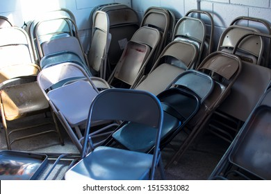 Stacks and Rows of Metal Steel Iron Different Color Collapsible Fold Up Folding Chairs Falling and Leaning against a Brick Cinder Block Wall with One Blue Chair Sitting in the Middle of a Storage Room
