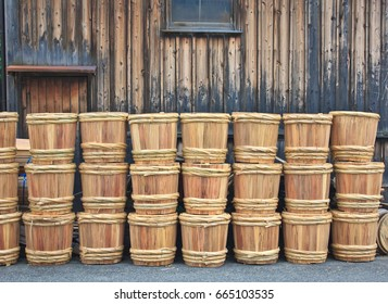 Stacks of traditional wooden sake barrels with bamboo hoops are piled up on the street behind a sake brewing factory warehouse in Japan.