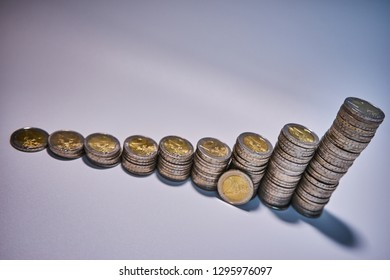 Stacks of two euro coins that start small on the left and get bigger to the right side isolated on a white background