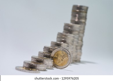 Stacks of two euro coins that start small in the foreground and get bigger in the background isolated on white
