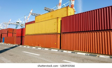 Stacks of various shipping container brands on a holding platform.