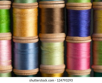 Stacks of Vintage Threads on Wooden Spools as a closeup background.