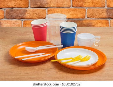 Stacks of the white and orange disposable plastic plates different sizes with disposable plastic forks, spoons and knives on them, plastic and paper disposable cups on a wooden table