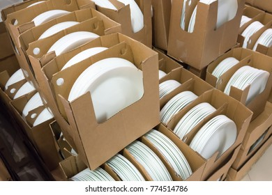 Stacks of white and round shaped porcelain plates in corrugated boxes.