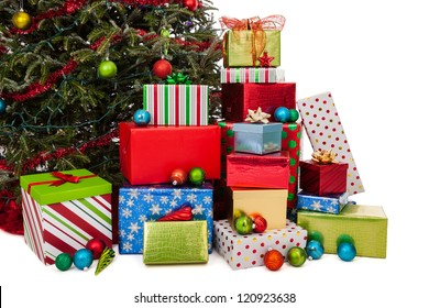 Stacks of wrapped Christmas gifts under the tree isolated on white