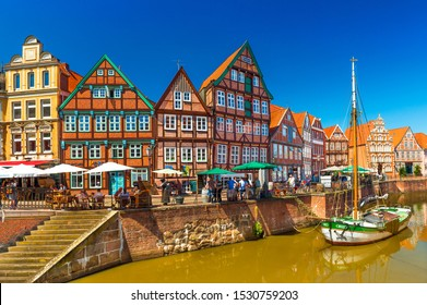 Stade - July 2019, Germany: Cityscape of a small, beautiful German town with the traditional half-timbered architecture and canal with an old wooden sailboat
