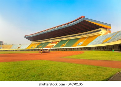 An  stadium with empty tribunes and grass brushed under blue sky in the southeast of China.