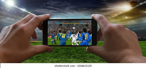 Stadium in the evening in full light before the match.   Football fan removes the football game on mobile phone