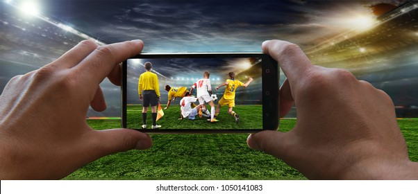 Stadium in the evening in full light before the match.   Football fan removes the football game on mobile phone 2018