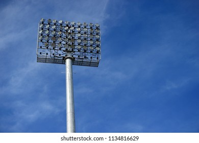 Stadium floodlight with metal pole with blue sky in the football stadium.