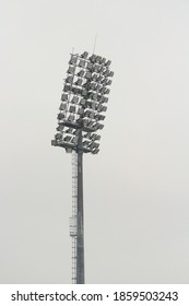 Stadium floodlight with metal pole, lighting mast, tower with floodlights in the sports stadium against the white sky