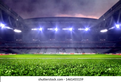 Stadium with green soccer field and bright spotlights at night