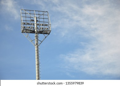 stadium light poles with white clouds and blue sky backgrounds