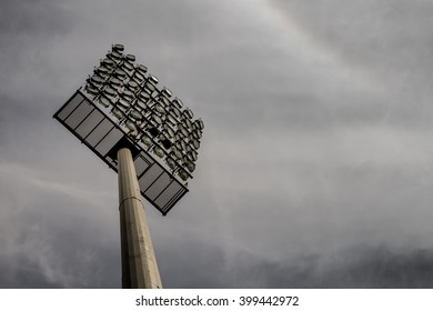 A stadium lighting tower with around fifty floodlights seen from below looking up the stand and into a stormy, gray sky.