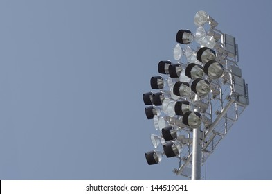 Stadium lights during daylight against blue sky with room for text