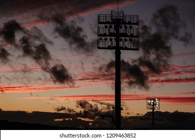 Stadium lights or lampposts silhouette in sunset hour with very dramatic and colourful clouds scene. Make your bets before tonights big game. Whether it is baseball, soccer or rugby.