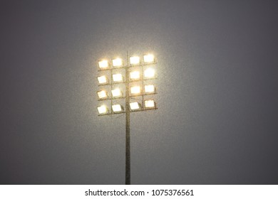 Stadium lights on pole, outdoors, snowy night. Dark sky in contrast to intense lights.