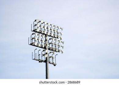 Stadium lights and speakers on a tall steel tower