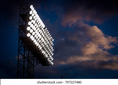 Stadium Lights standing tall in the clouds on a summer night.