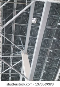 Stadium ventilation system and fire extinguishing system between the steel roof supports standing on concrete beams. Complex multi-system engineering structures.