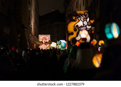 Stadthausgasse, Basel, Switzerland - February 19th, 2018. View from behind a marching carnival group on colorful illuminated lanterns during the morgestraich parade.