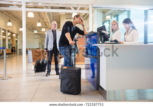 Staff Checking Passport Of Male Passenger At Counter In Airport